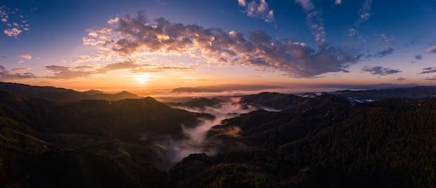 Panorama sobre o nascer do sol com fundo de céu azul no tempo de manhã e montanha nevoeiro no inverno