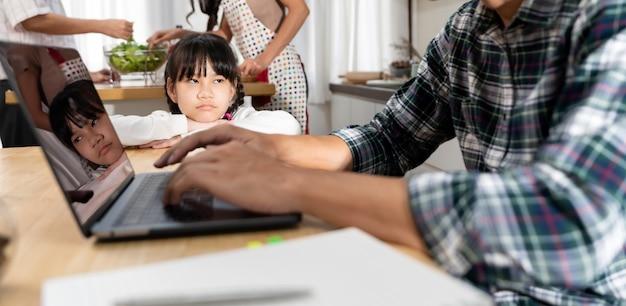 Panorâmica asiática chateada esperando o pai trabalhando em casa