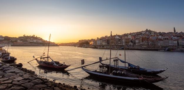 Panorâmica da paisagem urbana de porto no pôr do sol com o rio na frente e navio transportador de vinho em primeiro plano e cidade do porto em segundo plano, portugal