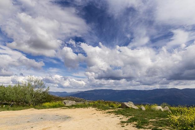 Panorâmica de algumas belas montanhas verdes com caminhos e pedras