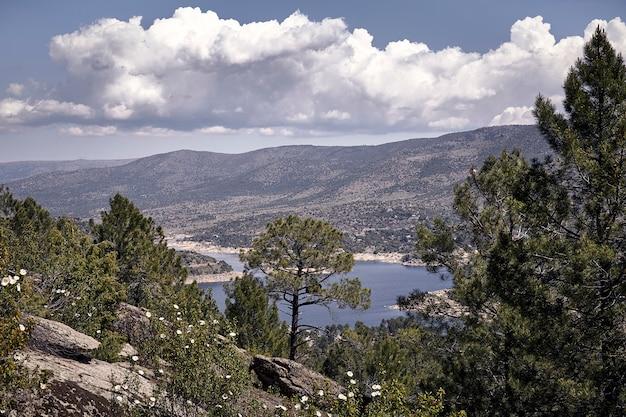 Panorâmica de algumas montanhas sob um céu azul nublado em uma manhã de primavera