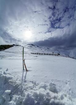 Panorâmica vertical da paisagem de alta montanha nevada com o sol nascer do sol e nuvens. la morcuera.