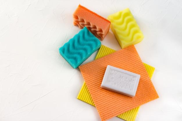 Panos coloridos, esponjas e pedaço de sabão branco sobre fundo branco com copyspace