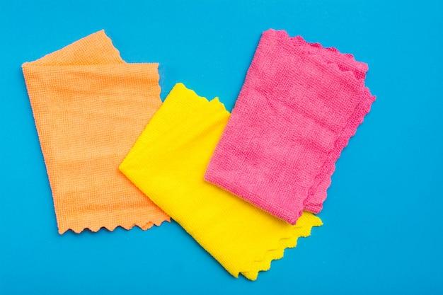 Panos de microfibra dobrados coloridos sobre um fundo azul. conceito de equipamento de limpeza