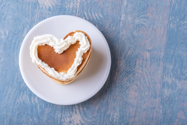 Panqueca caseira em forma de coração decorada com creme branco em um prato branco sobre fundo azul de madeira