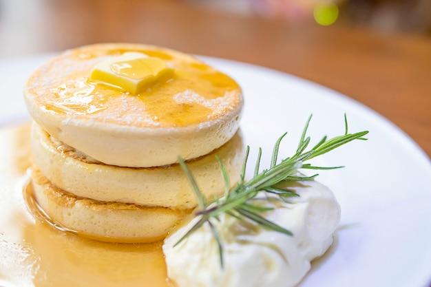 Panqueca com manteiga derretida e xarope no topo