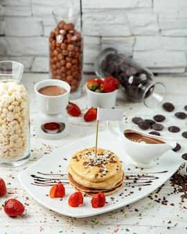 Panqueca com morangos e chocolate em cima da mesa