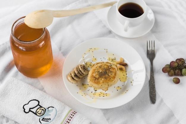 Panqueca; com pote de mel; xícara de café na toalha de mesa