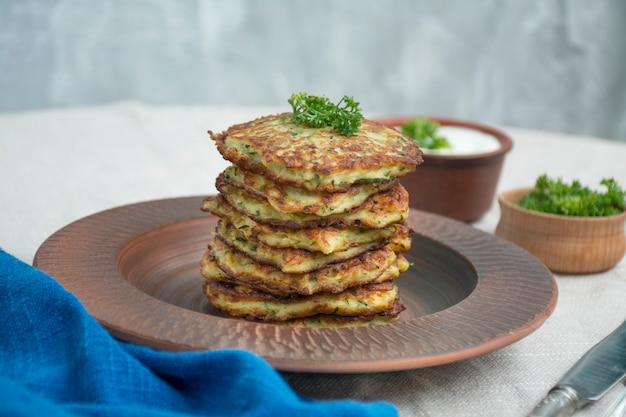 Panqueca de abrobrinha. panquecas de abobrinha vegetariana com ervas frescas e creme de leite. uma pilha de panquecas. mesa de jantar. equilibre alimentos saudáveis. luz de fundo.