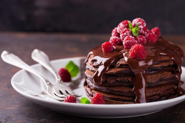 Panqueca de chocolate com cobertura de chocolate, framboesas e hortelã.