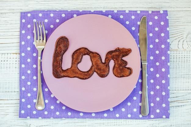 Panqueca de chocolate num prato. o conceito de comida e amor.