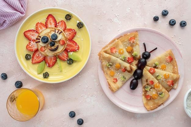 Panqueca de flores engraçadas com frutas vermelhas para o café da manhã das crianças