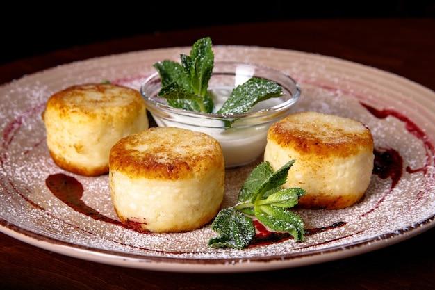 Panqueca de queijo, bolos de queijo com creme de leite, geléia e hortelã em um prato. cafe da manha.