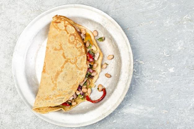 Panqueca de trigo sarraceno saboroso com feijão branco, pimentão vermelho e amarelo, salsa e frango. quesadilla mexicana. vista do topo. copie o espaço.