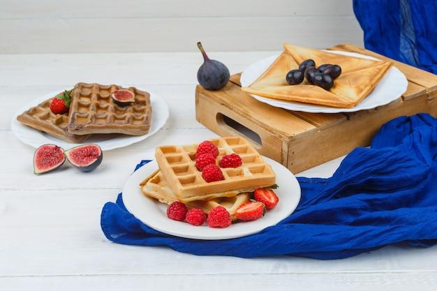 Panqueca em prato branco com figos e waffles com morangos