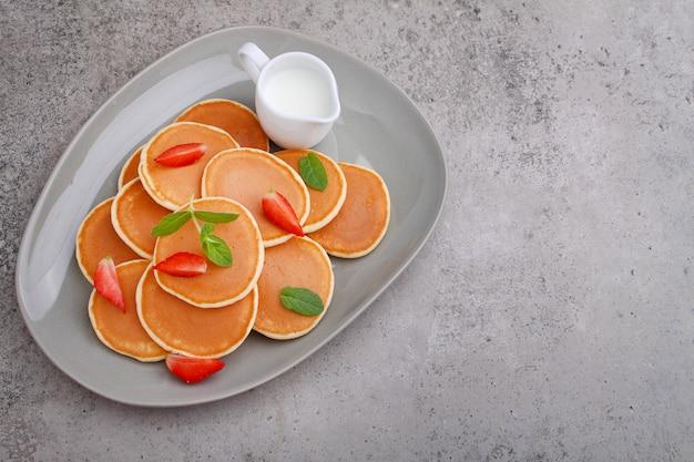 Panqueca em um prato com morangos decorados com hortelã em uma mesa de concreto