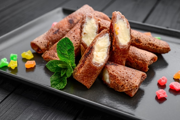 Panqueca fina e doce com chocolate, queijo cottage e frutas, em uma superfície preta