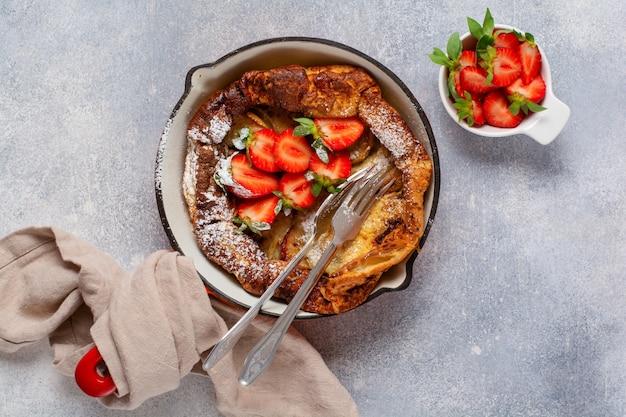 Panqueca holandesa de bebê com baga de morango fresca e polvilhada com pó de açúcar de confeiteiro na panela vermelha sobre fundo branco da cozinha. vista do topo.