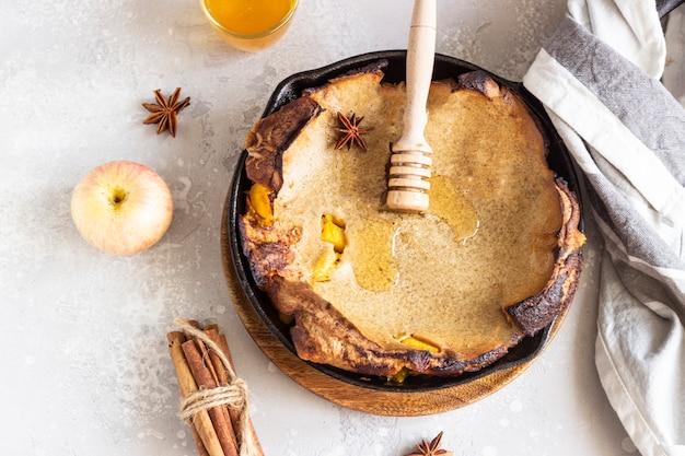Panqueca holandesa integral com maçã, mel e especiarias (canela e anis). delicioso café da manhã de outono ou inverno.