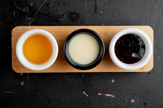 Panqueca, molhos, mel, leite condensado, baga, geléia, vista superior