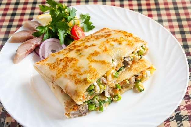 Panqueca quente com arenque e legumes em um prato branco