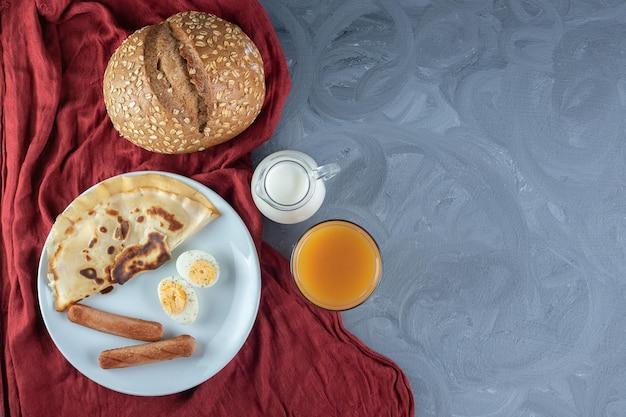 Panqueca, salsichas e fatias de ovo cozido ao lado de leite, suco e pão na mesa de mármore.