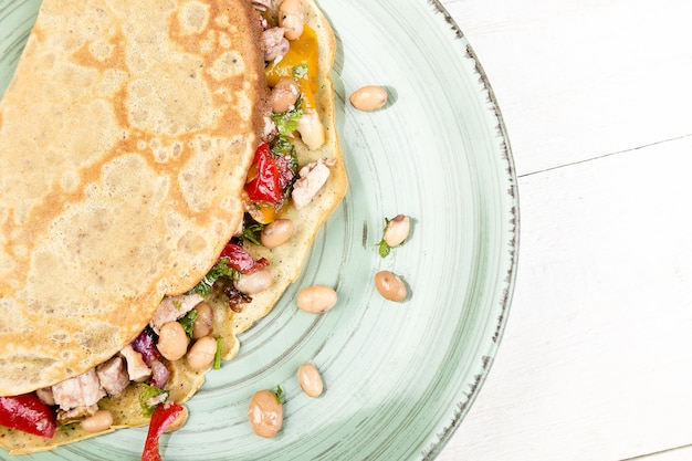 Panqueca savory do trigo mourisco com feijões brancos, pimenta de bell vermelha e amarela, salsa e galinha.