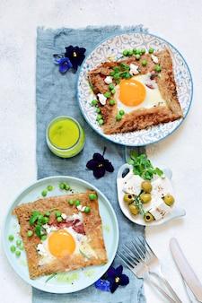 Panqueca tradicional bretã à base de farinha de trigo sarraceno com fiambre, queijo, ovo, queijo feta, ervilha e manteiga verde.