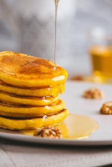 Panquecas amarelas com farinha de milho e cúrcuma, mel temperado e uvas vermelhas