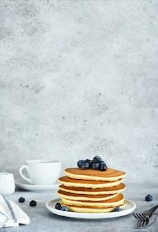 Panquecas americanas caseiras com frutas e xarope de bordo no café da manhã em um fundo de concreto.