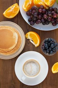 Panquecas americanas caseiros com xícara de café e frutas. mesa de madeira.