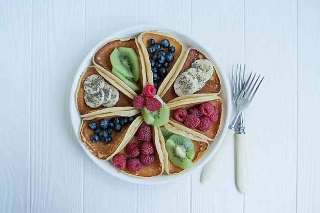 Panquecas americanas clássicas com bagas frescas em um azul de madeira. panquecas com frutas. café da manhã caseiro de verão. .