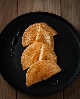 Panquecas americanas ou crepes no prato preto no café da manhã