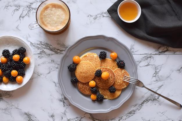 Panquecas café da manhã saudável sem glúten blackberry physalis mel cappuccino café mármore vista superior lay plana