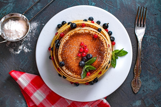 Panquecas caseiras assadas doces com frutas, hortelã e açúcar de confeiteiro no café da manhã. vista do topo