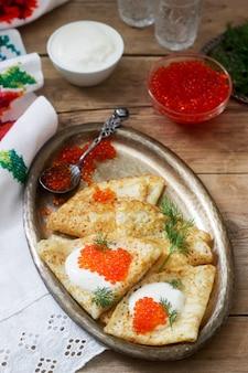 Panquecas caseiras com caviar vermelho, creme de leite e endro, servidos com vodka. estilo rústico.
