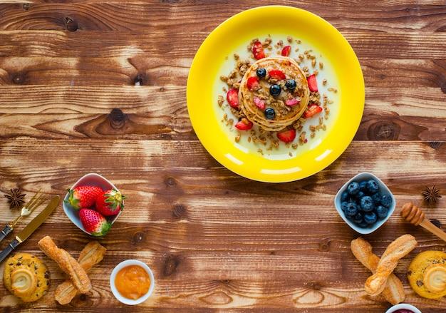 Panquecas caseiras com frutas frescas, morangos, mirtilos e xarope de bordo.
