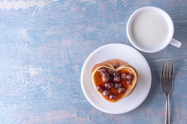 Panquecas caseiras em forma de coração com geléia de frutas vermelhas, copo de leite branco e garfo na mesa de madeira azul
