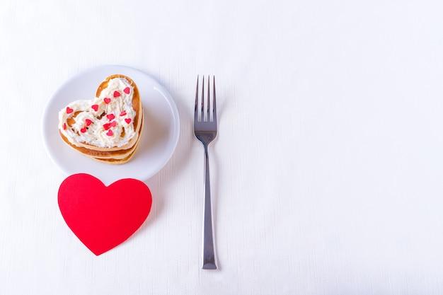 Panquecas caseiras em forma de coração decoradas com creme e doce de açúcar em um prato branco, garfo e formato de coração vermelho em branco sobre fundo branco