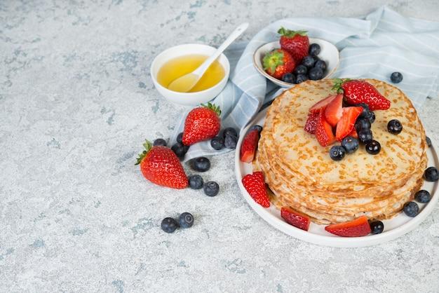 Panquecas caseiras finas em um prato com frutas frescas e mel, copie o espaço