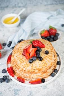 Panquecas caseiras finas em um prato com frutas frescas e mel.