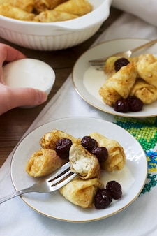 Panquecas caseiras recheadas com queijo cottage com passas, servidas com creme de leite e cereja.
