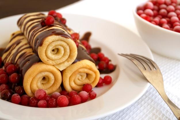 Panquecas caseiras torcidas com chocolate num prato branco.