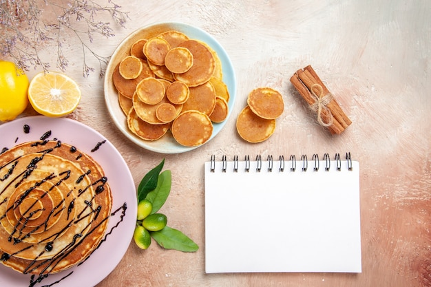Panquecas clássicas simples e decoradas com frutas e caderno