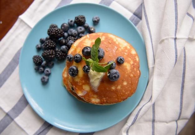 Panquecas com amoras, mirtilos e hortelã em um prato azul - vista superior