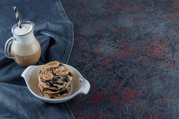 Panquecas com banana e chocolate em uma tigela branca com um café delicioso.