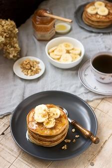 Panquecas com banana, nozes e mel, servidas com chá. estilo rústico.