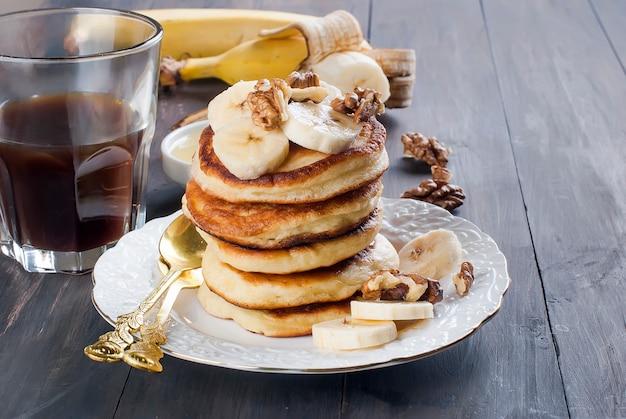 Panquecas com banana, nozes, mel e xícara de café em fundo escuro
