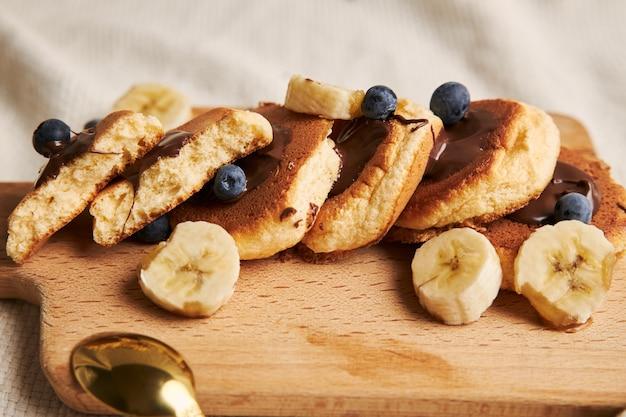 Panquecas com calda de chocolate, frutas vermelhas e banana em um prato de madeira