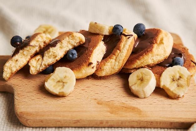 Panquecas com calda de chocolate, frutas vermelhas e banana em uma placa de madeira atrás em branco